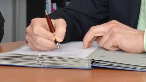Ein Konsortialvertrag wird unterzeichnet.