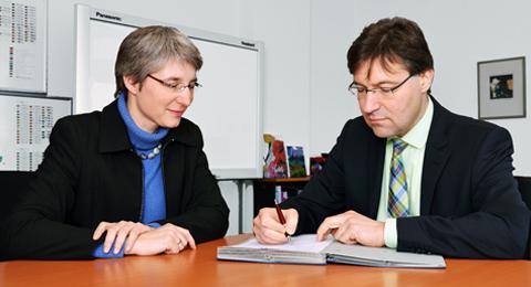 Anne-Kathrin Triebel legt Kanzler Frank Eisoldt einen Konsortialvertrag zur Unterschrift vor.